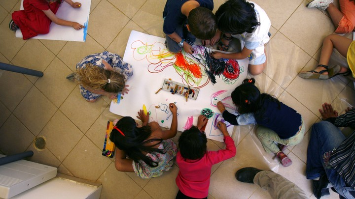 Preschoolers scribbling with markers and crayons on a large white paper