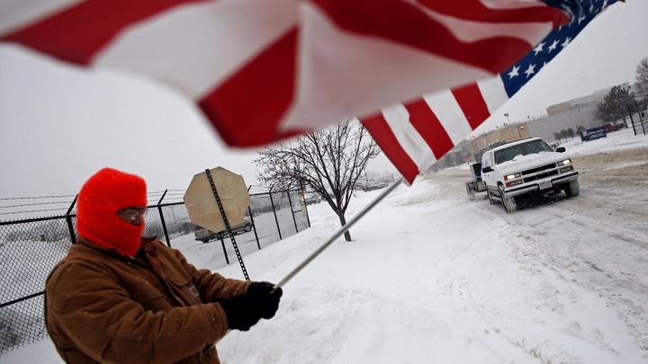 Two days before Christmas of 2008, a resident of Janesville waves a flag outside of the General Motors assembly plant in solidarity with the laid-off workers leaving the plant on its final day in operation.