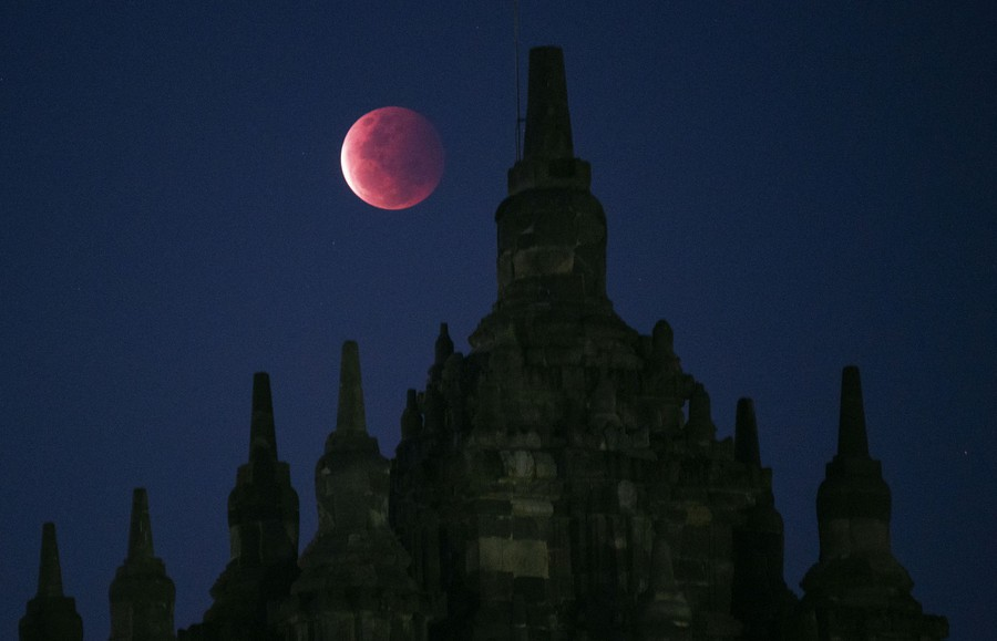 A pink full moon above a temple