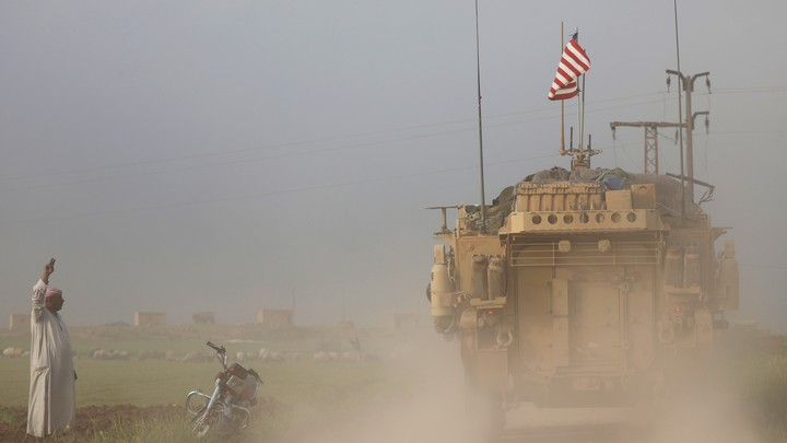A man gestures at U.S military vehicles near the Turkish border of Syria on April 28, 2017.