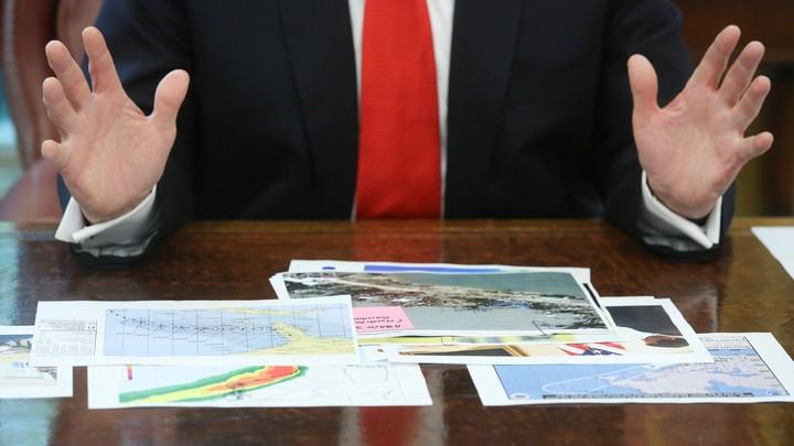 President Trump looks at hurricane-prediction documents.