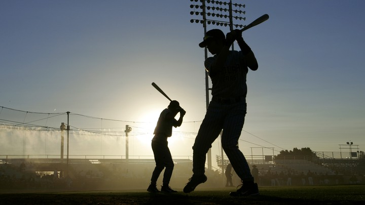 The silhouettes of swinging baseball players