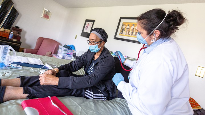 An in-home nurse cares for a woman while she recovers from COVID-19 at her home in Baltimore, Maryland.