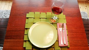 A place setting for one: A light green plate on a green woven placemat with a knife and fork sitting on a plaid napkin. A half-full glass of wine sits by the plate.