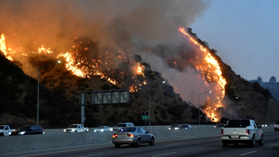 A fire burns on a hillside next to a freeway as cars drive by.