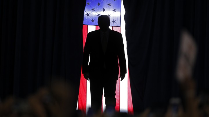 Trump is silhouetted against an American flag