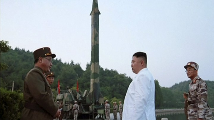 Kim Jong Un and a missile launcher in North Korea
