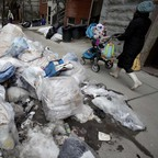 A woman pushes a stroller past a pile of garbage bags on a snow bank next to a New York City sidewalk.