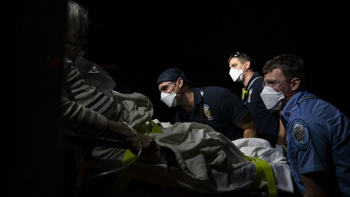 Paramedics prepare to transport a coronavirus patient to the hospital.