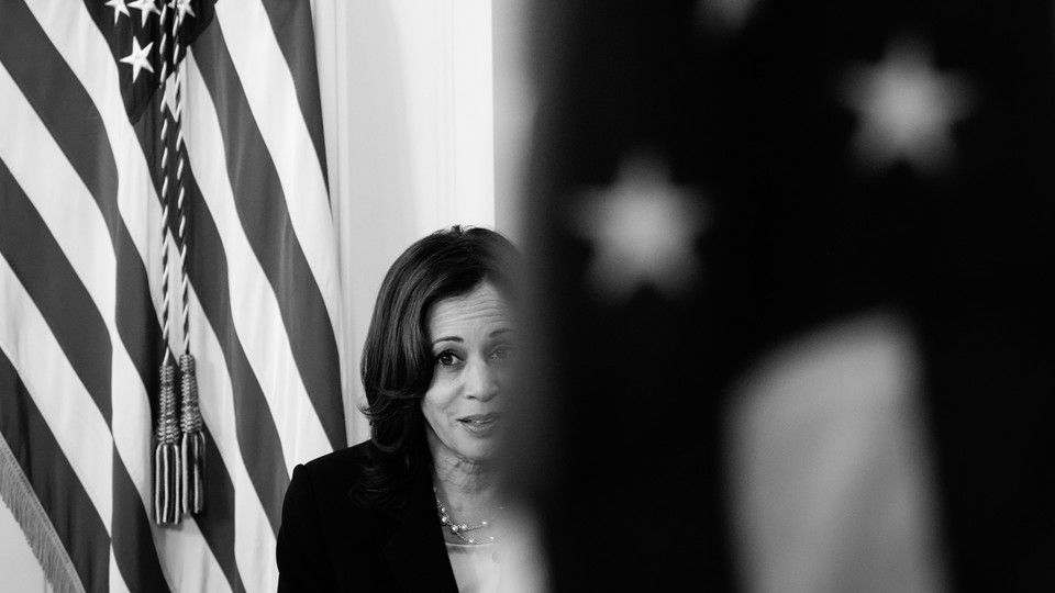 Vice President Kamala Harris is seen between two flags; one is blurred in the foreground and obscuring part of her face, and the other is just behind her.