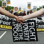 Clasped hands in front of a banner at the Poor People's Campaign rally in Washington, D.C. on Saturday, June 23, 2018,
