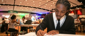 A young man fills out an application at a Chicago job fair.