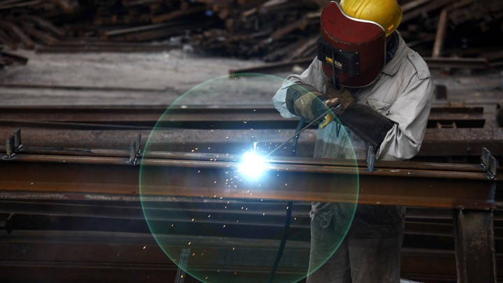 Someone works in a factory. The worker's face is covered with a protective helmet. A flash of light flickers.