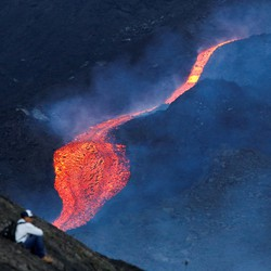 A person sits alone on a hillside watching lava flow.