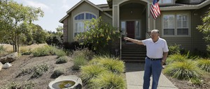 A man shows off his garden, designed to use less water, in front of his home in Santa Rosa, California.