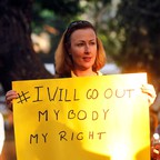 """A woman holds a sign that says """"#I Will Go Out My Body My Right."""