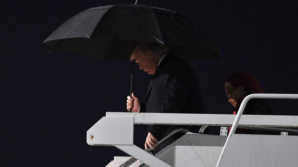 President Trump carrying a black umbrella as he disembarks Air Force One