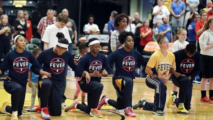 Indiana Fever kneel during the national anthem