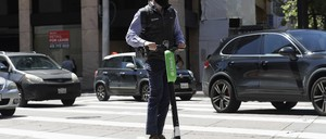 A man rides a motorized scooter as he approaches Market Street in San Francisco, Tuesday, April 17, 2018.