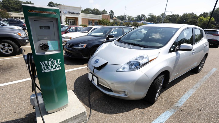 An electric vehicle at a Whole Foods–branded charging station