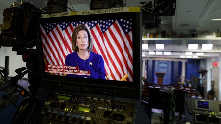 Nancy Pelosi appears on a video screen at the back of the White House press briefing room.