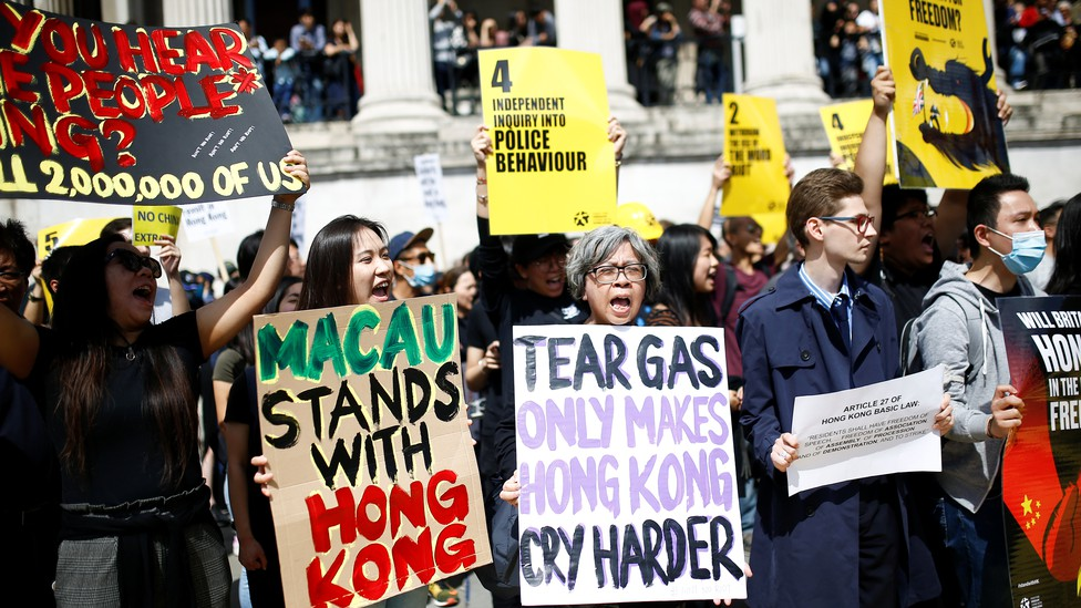 """Supporters of the Hong Kong protests hold signs reading """"Macau stands with Hong Kong"""" and """"Tear gas only makes Hong Kong cry harder."""""""