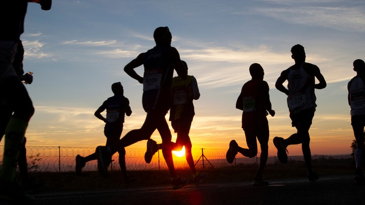 Silhouettes of people jogging along a road