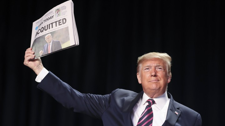 """Trump displays a newspaper reading, """"Acquitted"""""""