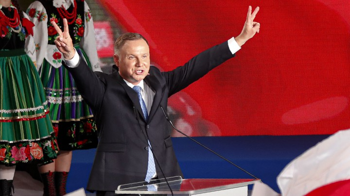 The newly reelected president of Poland, Andrzej Duda, holds his hands up in victory