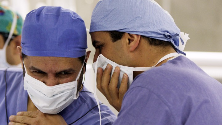 Former Saudi Health Minister Abdullah al-Rabia and a doctor, pictured in scrubs and surgical masks, consult during a surgery in 2010.