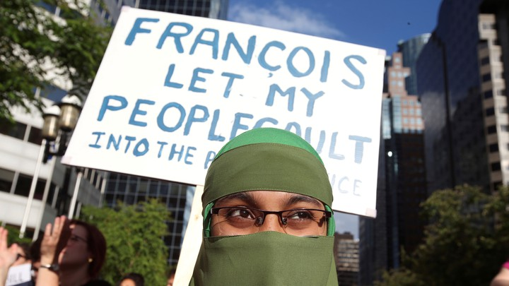 A woman in a niqab holds a placard at a protest.