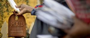 U.S. Postal Service letter carrier Jamesa Euler delivers mail on Thursday, Feb. 7, 2013, in Atlanta.