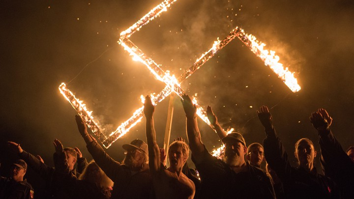 Supporters of the National Socialist Movement give Nazi salutes while taking part in a swastika burning.