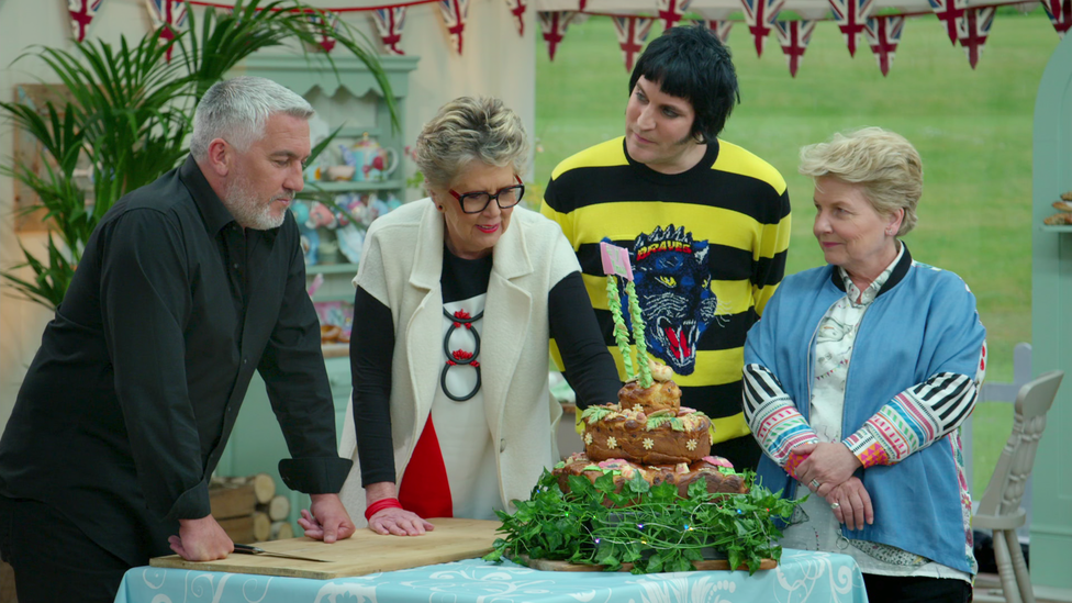 """The hosts and judges of """"The Great British Baking Show"""" examine a cake."""