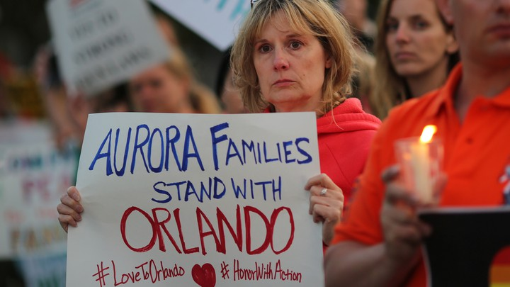 "A woman at a candlelight vigil holds a sign reading ""Aurora families stand with Orlando."""