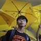 Joshua Wong stands in front of yellow umbrellas, the symbol of the 2014 Hong Kong protests, ahead of a 2015 court hearing.