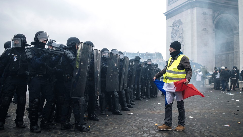 A protester stands in front of riot police at the Arc de Triomphe on January 12.