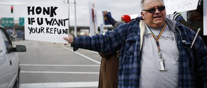 A photo of an IRS tax examiner protesting outside his office during the partial government shutdown in January.