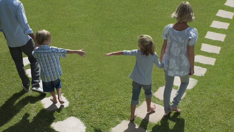 A man and woman lead two small children away from each other by the hand.