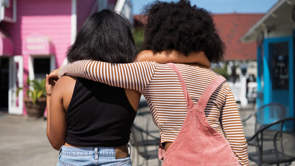 Friends stand with their arms around each other.
