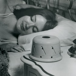 A black-and-white image of a woman sleeping next to a sound conditioner