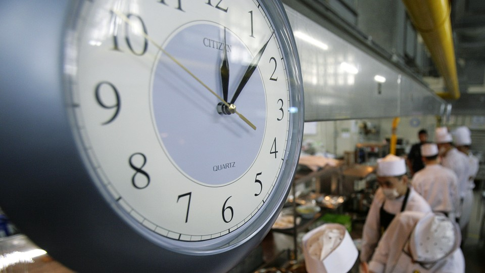 A clock above a busy kitchen