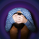 A child holding their head in the fetal position against a background of purple concentric circles