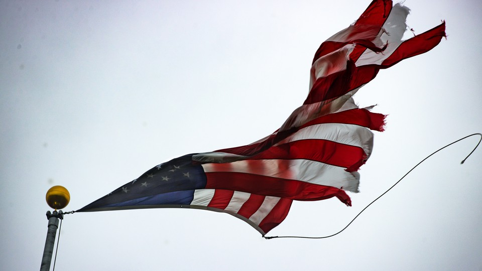 A tattered American flag flying atop a flagpole with a bronze-colored topper