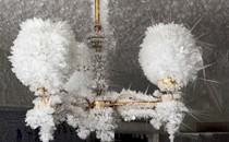 Ice crystals completely cover a small chandelier and the ceiling it hangs from.