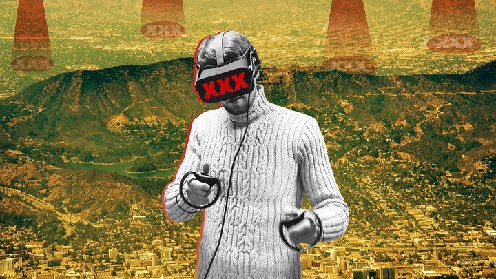 """A man wearing a cable-knit sweater wears virtual-reality goggles labeled """"XXX."""""""
