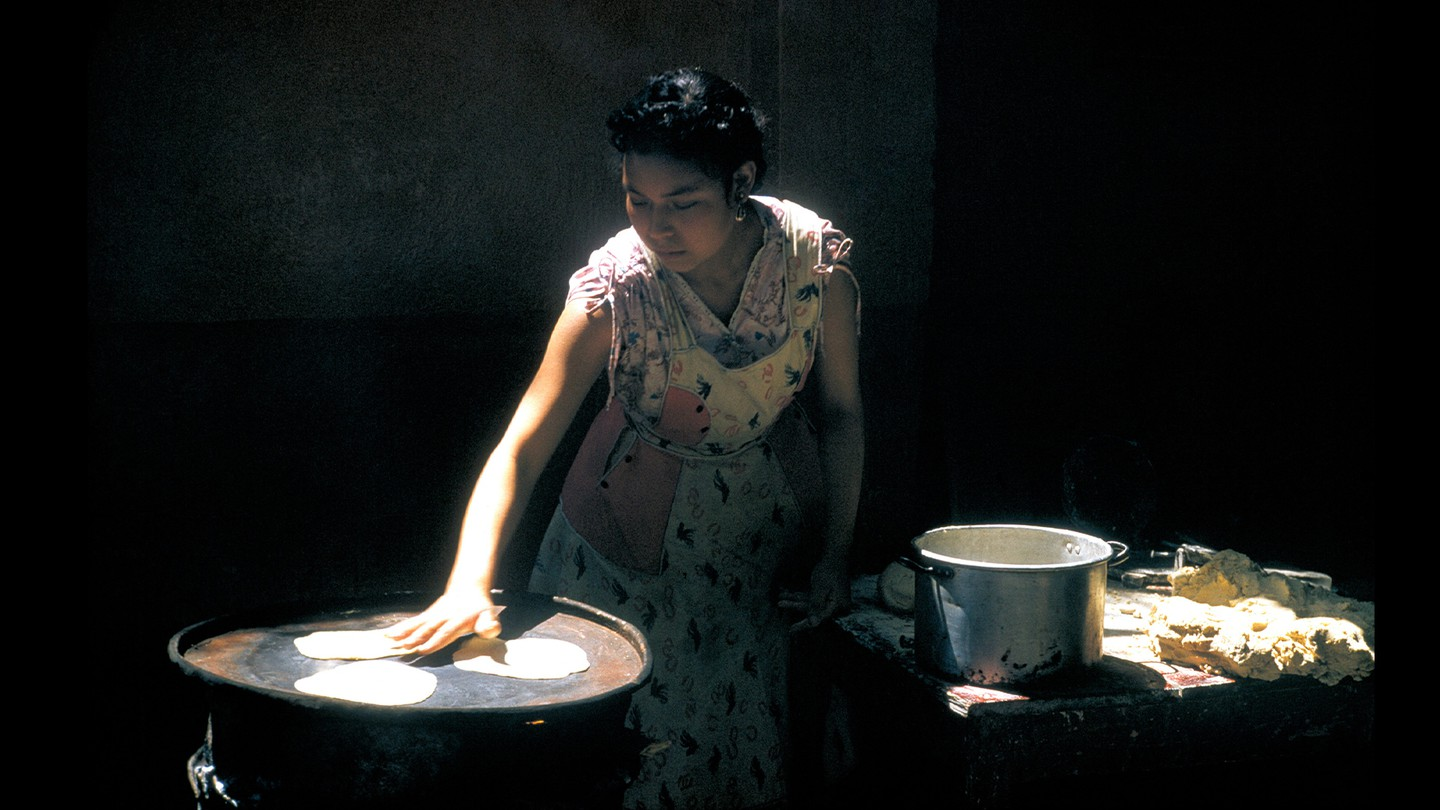 A woman lit by a ray of light against a black background lays out tortillas she's cut from dough