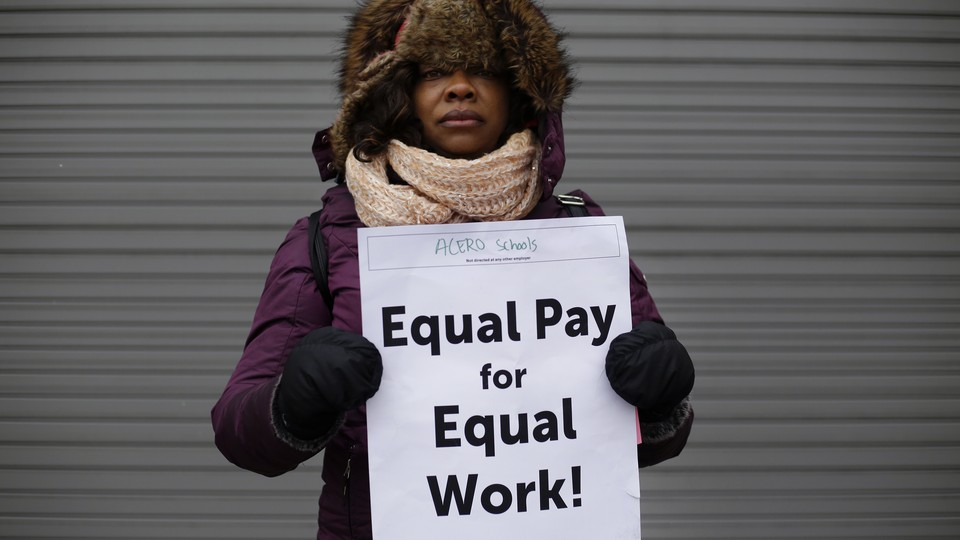 """A woman holds a sign saying """"Equal pay for equal work"""""""