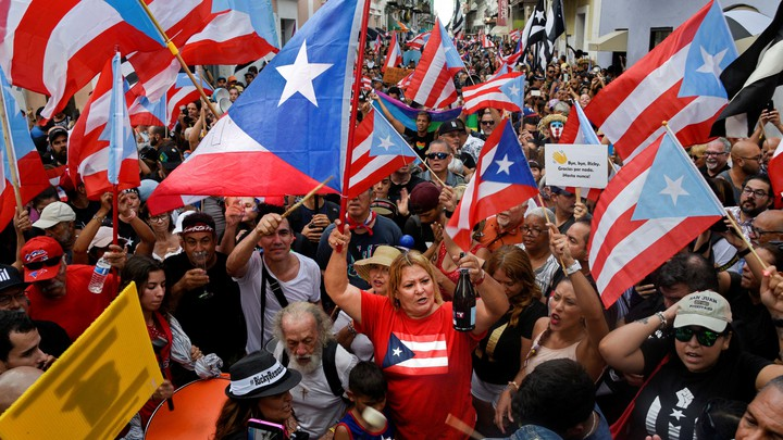 A crowd waving Puerto Rican flags