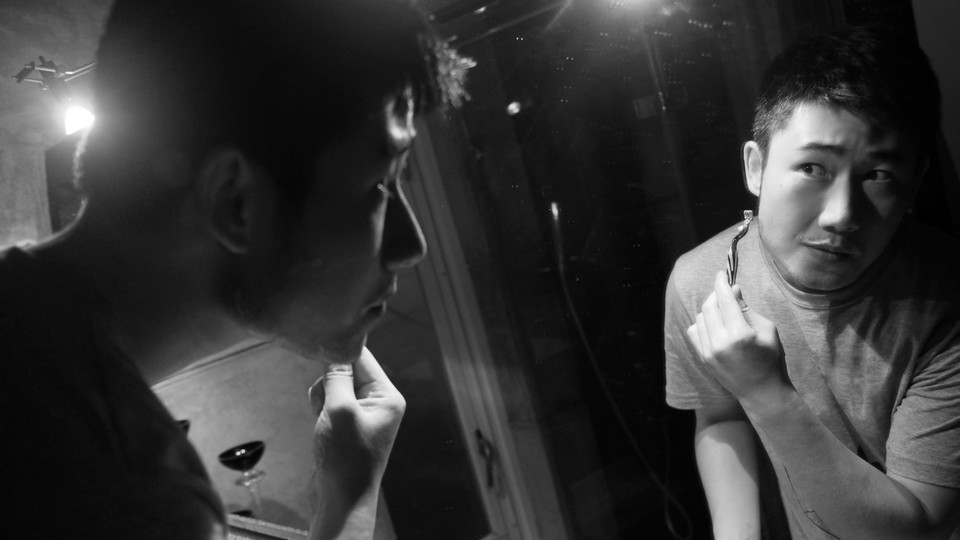 A young man shaves while looking in the mirror